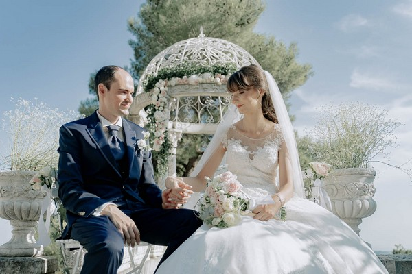 bride and groom seated hand in hand in front of garden rotunda decorated with pink roses