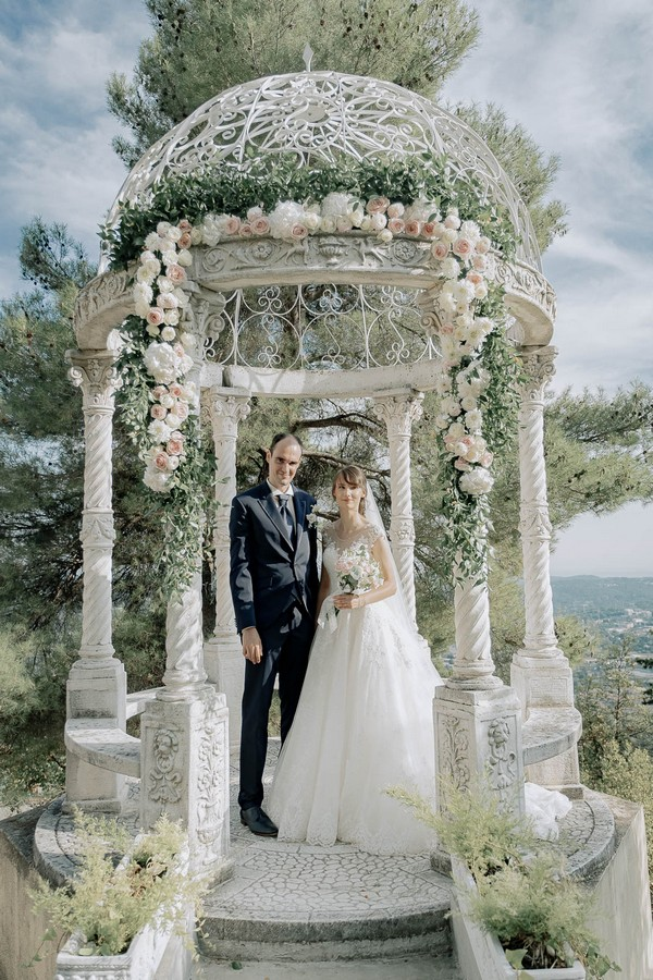 bride and groom in floral decorated rotunda overlooking a valley