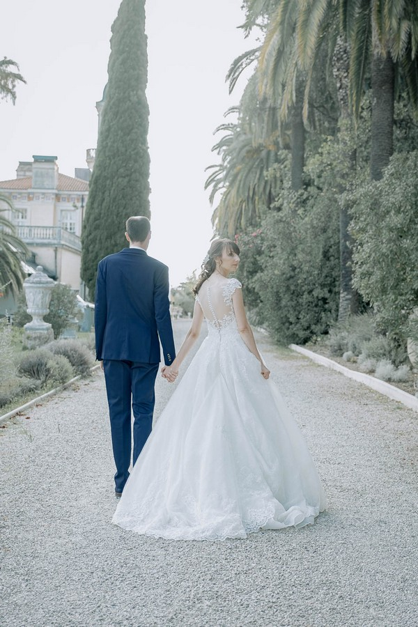 bride and groom walking away from camera along pebble path in garden of chateau