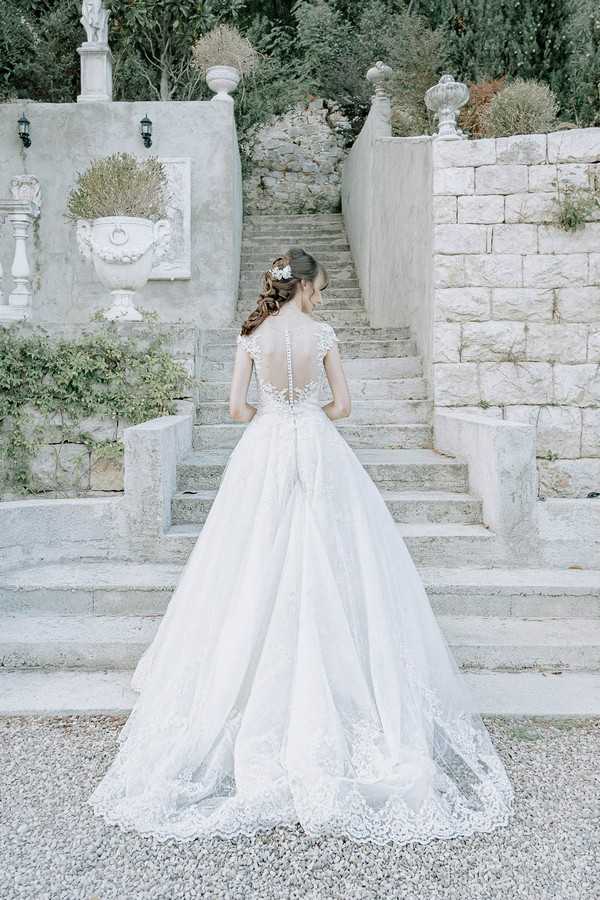 bride shows the back of her dress to camera it is made of white lace and has buttons up to the nape of her neck
