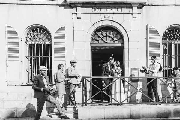 black and white image of bride and groom kissing outside town hall surrounded by guests