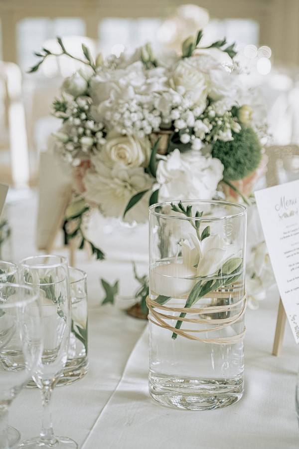 floral decorations for wedding table including vase of white flowers and a glass of water with small flower trimmings in it