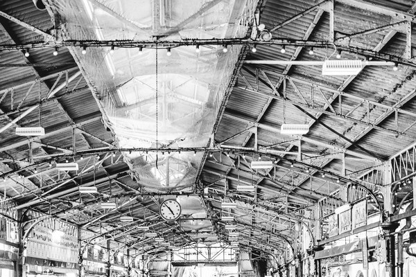 Black and white image of steel beams on factory ceiling