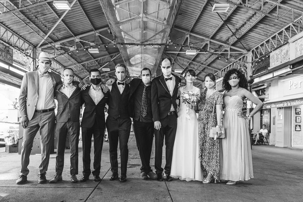 black and white image of bride and groom standing with their groomsmen and bridesmaids wearing face masks