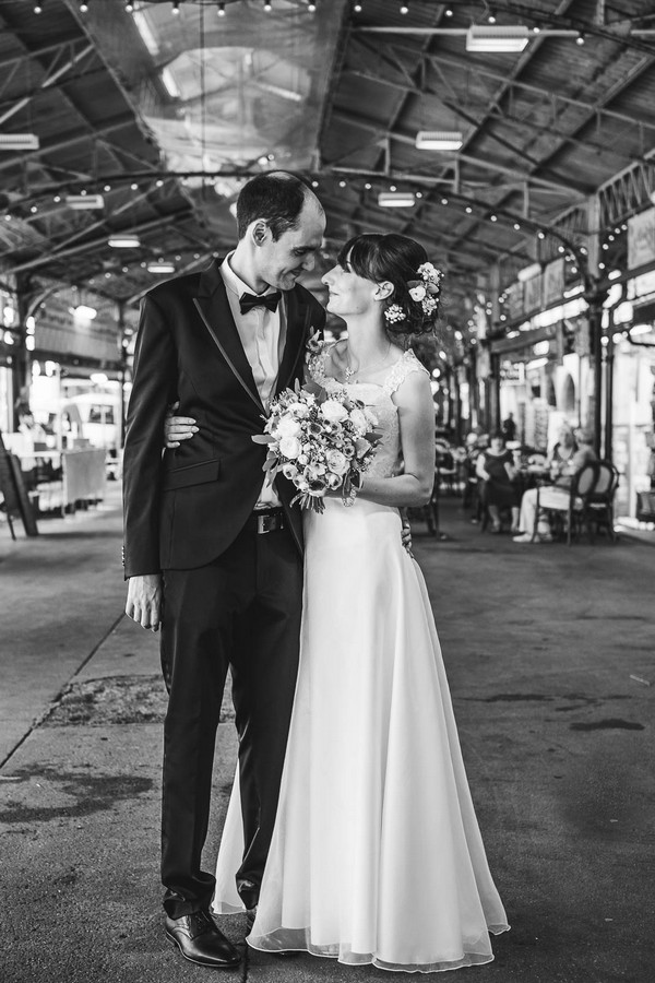 black and white image of bride and groom smiling at each other in industrial space with steel beams