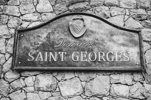 """Black and white image of iron sign that says """"Domaine Saint Georges"""""""