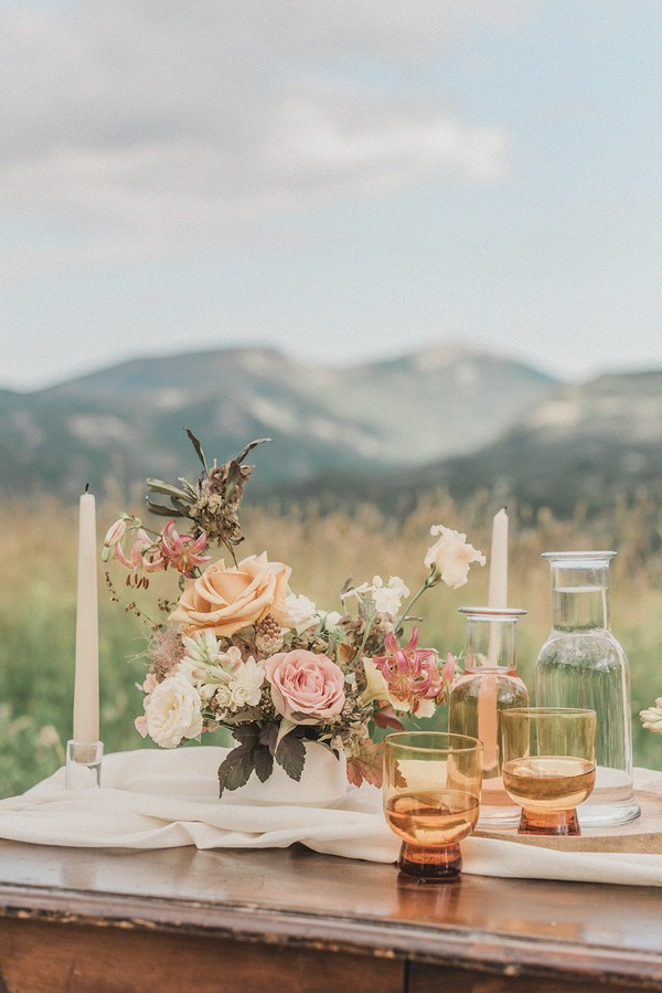 simple couples wedding table arrangement on dark wood table in a field with mountain views