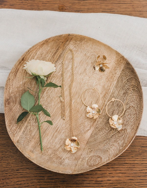 flat lay of white rose, gold flower hoop earrings and matching necklace and ring in rustic wooden serving platter
