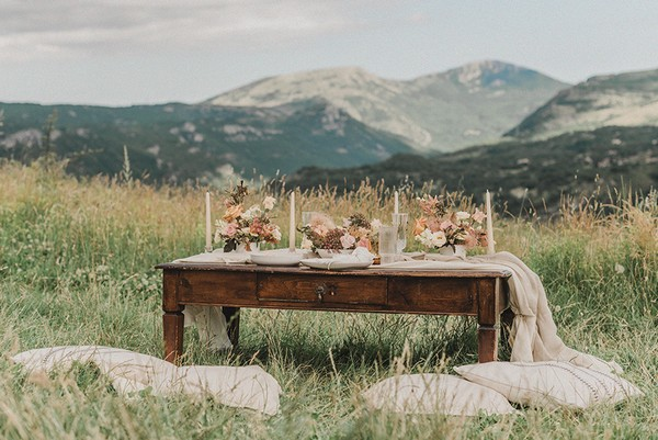 low dark wood coffee table with cream fabric, candles and pastel floral arrangement in field with mountain views