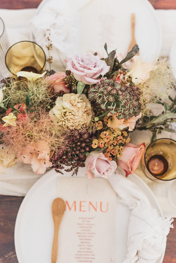 pink and cream wedding menu with small wooden spoon and pastel floral arrangement