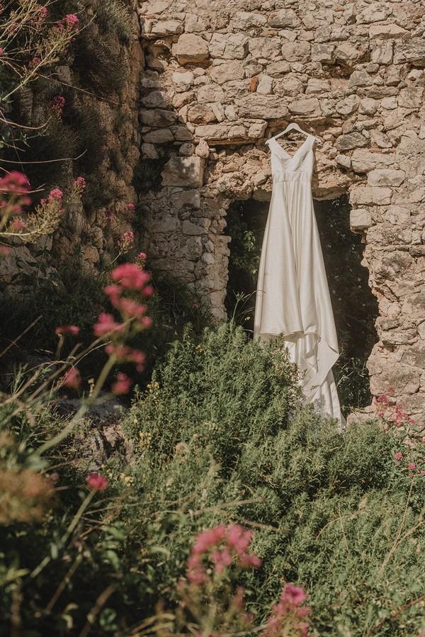 wedding dress hanging from doorway in old castle ruins