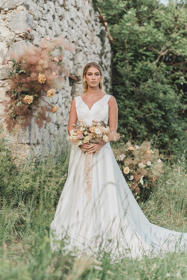 bride stands in front of stone castle ruins holding cream bouquet