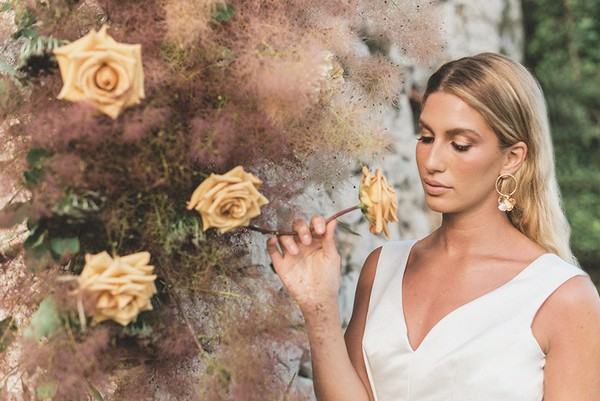 bride leans into to smell yellow roses and wears gold flower hoop earrings