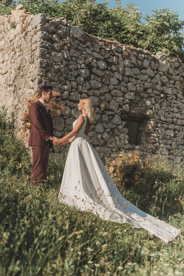bride and groom meet in front of stone ruins her dress trails behind her and he wears a burgundy suit