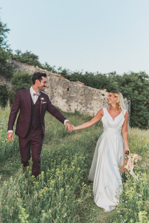 bride and groom hold hands and walk through green field with stone ruins visible behind them
