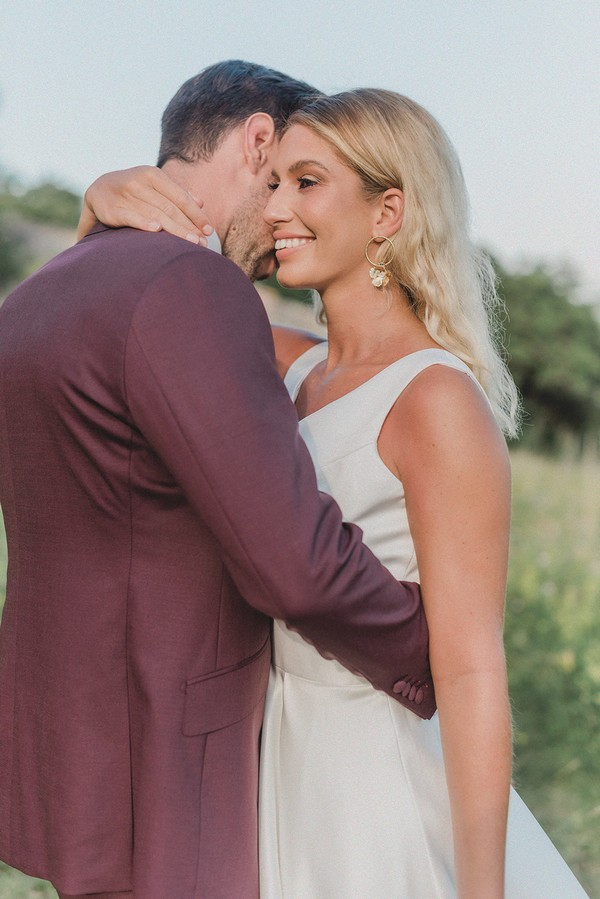 bride and groom embrace with a grey sky visible he is in a burgundy suit and she is in a white dress