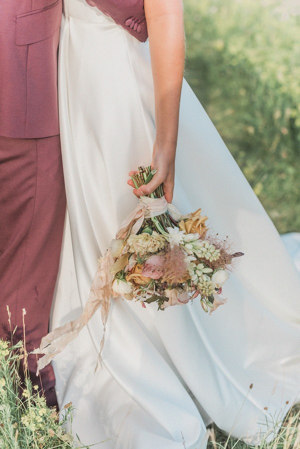 brides arm hangs by her side holding cream and pastel bouquet of flowers