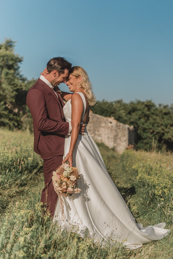 bride and groom hug and smile standing in a green field with stone ruins behind them