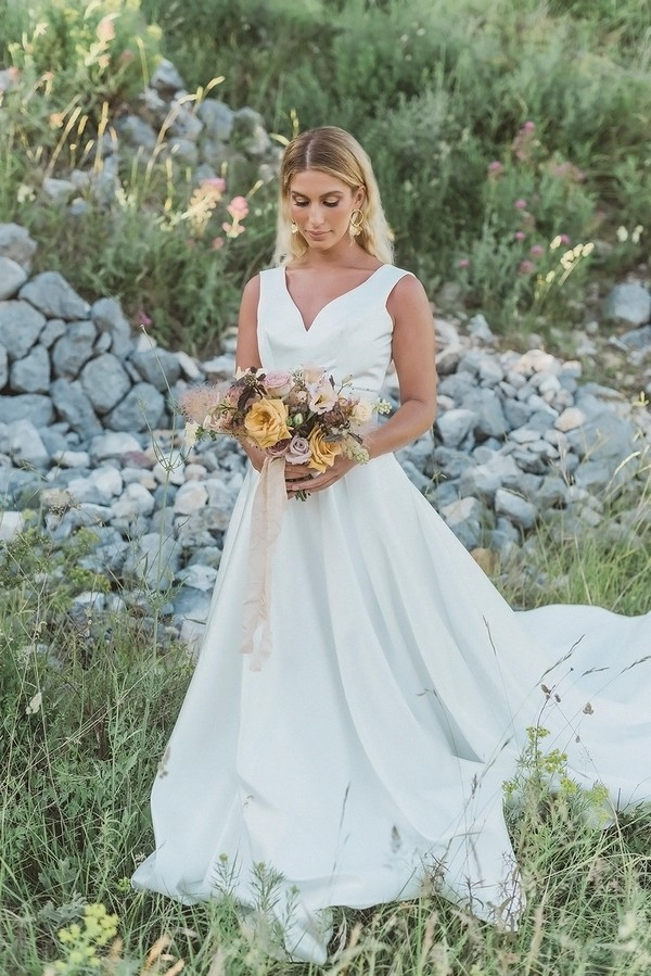 bride in white dress looks down at her pastel bouquet with stones from castle ruins behind her