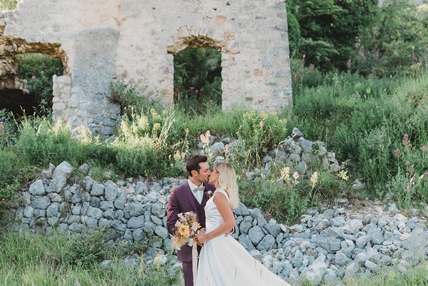 bride and groom kiss in front of stone ruins for their spring picnic wedding in the South of France