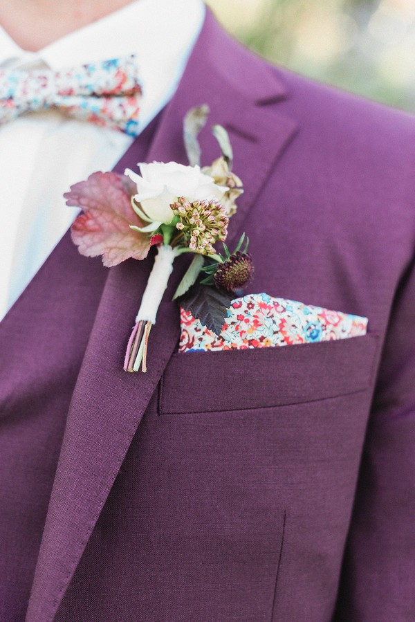 groom wears burgundy suit with white flower buttonhole and matching floral bowtie and pocket square