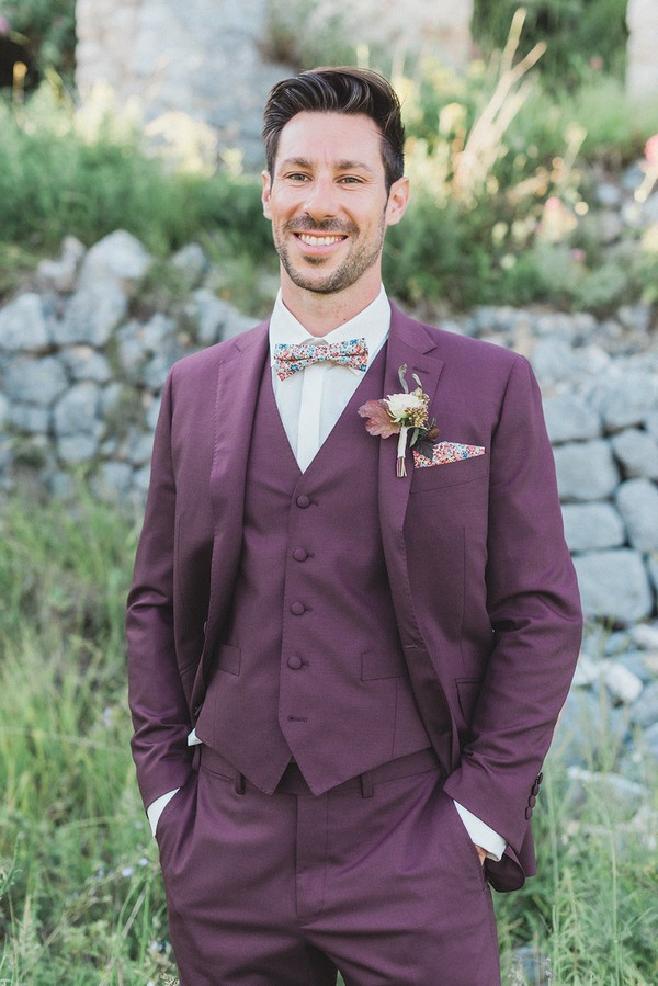 groom in burgundy suit and floral bowtie with matching pocket square smiles with hands in pockets