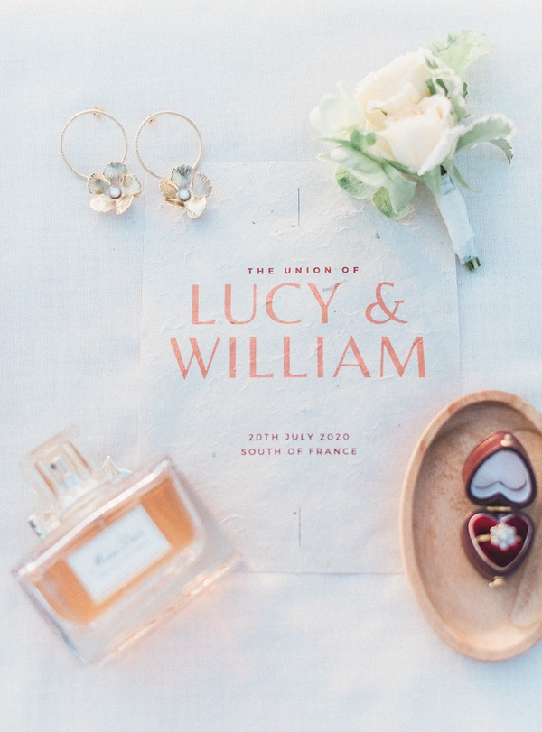 flat lay of perfume, flower earrings, white posie and ring in a heart shaped box on top of a wedding invite