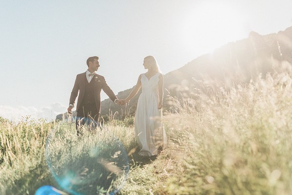bride and groom hold hands and walk through sundrenched yellowing field