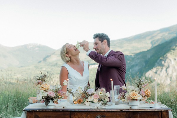 groom feeds his bride grapes as they sit on the ground in front of small decorated wedding table with rolling mountain views behind them