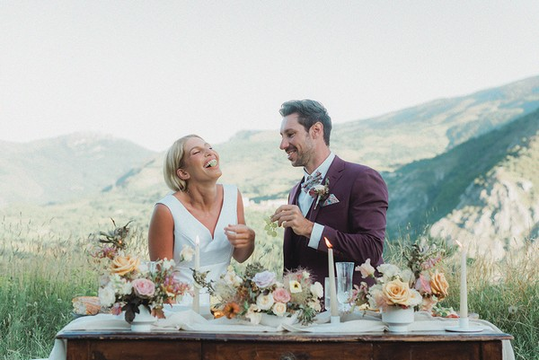 bride and groom at wedding table with rolling mountain views in background