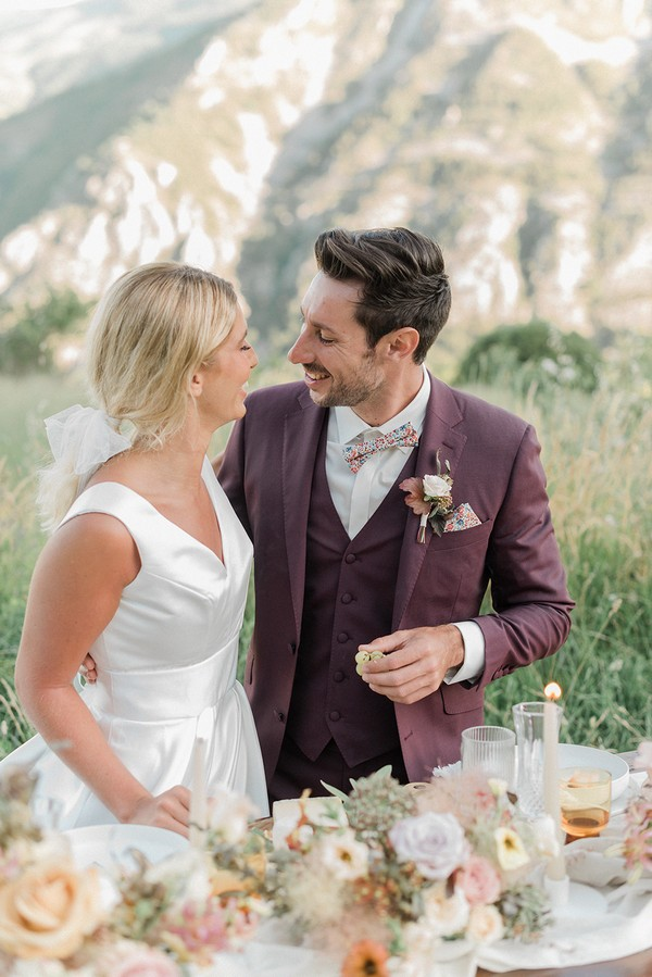 bride and groom smile at each other in a field for their spring picnic wedding