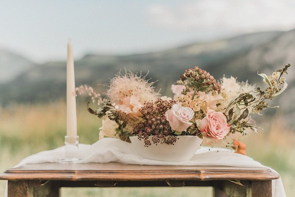 table with white candle and neutral toned floral arrangement in a field with mountain views