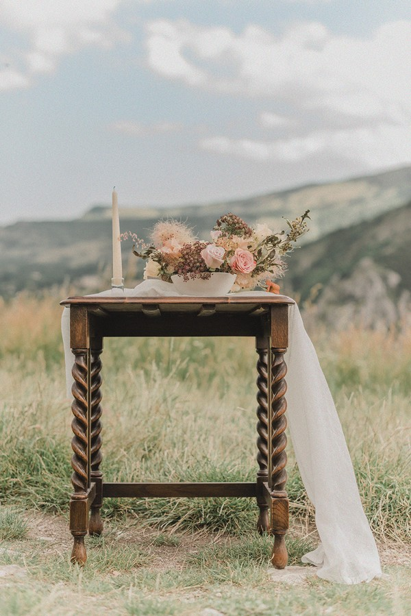 floral arrangement in a bowl and candle on old dark wood side table in field