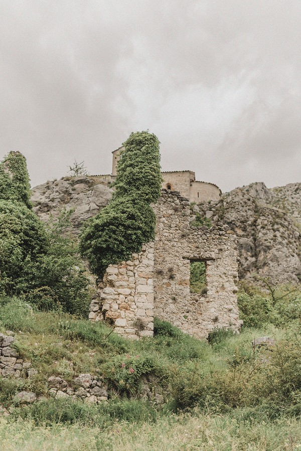 stone castle ruins overgrown by greenery