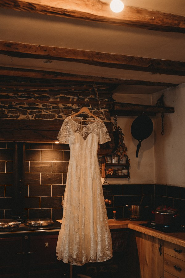 lace wedding dress hanging from old wooden beams inside farm house