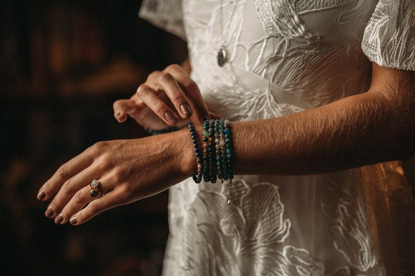 bride's arm with beaded green bracelets