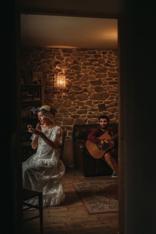 bride does makeup in handheld mirror and groom serenades her on his guitar