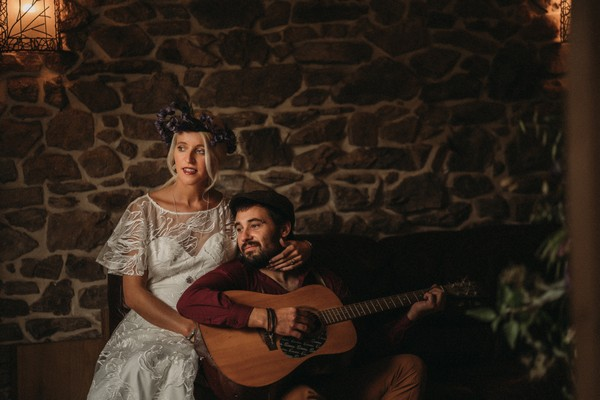 bride sits with groom on his guitar in front of stone wall