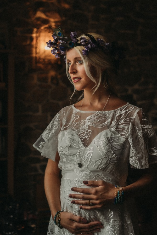 pregnant bride in lace dress and peacock feather crown holds her belly