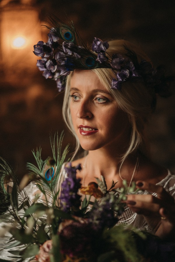 bride with purple flower and peacock feather crown and bouquet