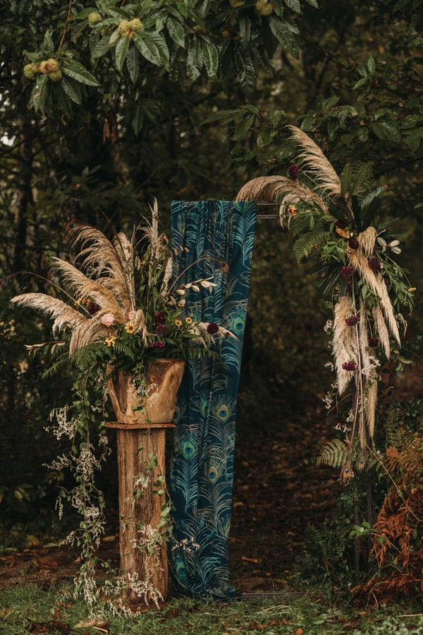 wedding altar made from peacock feather printed fabric and pampas grass