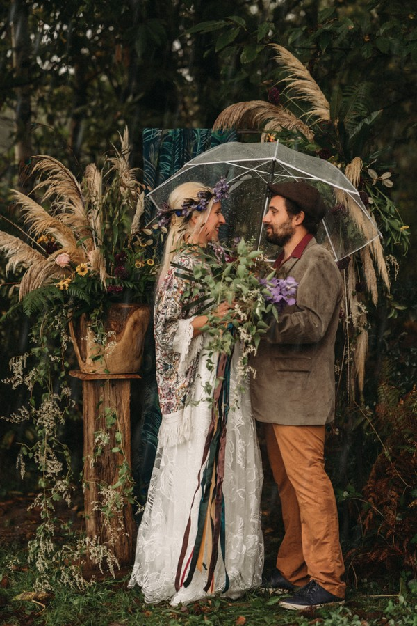 bride and groom surrounded by pampas grass under umbrella in the rain
