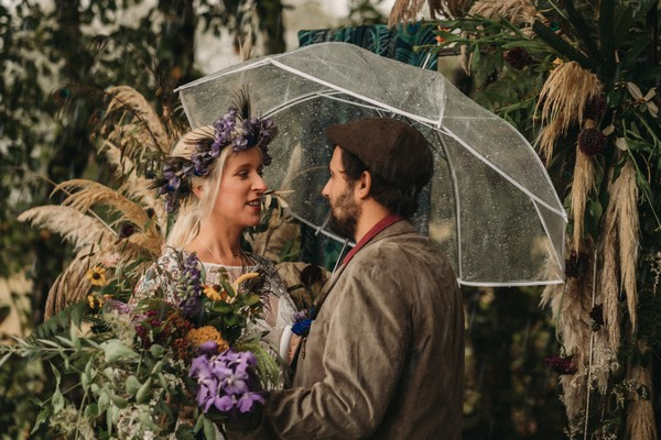 bride and groom under clear umbrella in rain surrounded by pampas grass and purple flowers