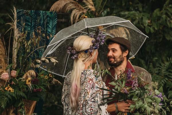 groom smiles at bride under umbrella in the rain