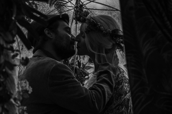 black and white image of bride and groom kissing under umbrella in rain
