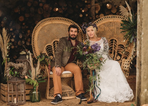 bride and groom on rattan peacock chairs