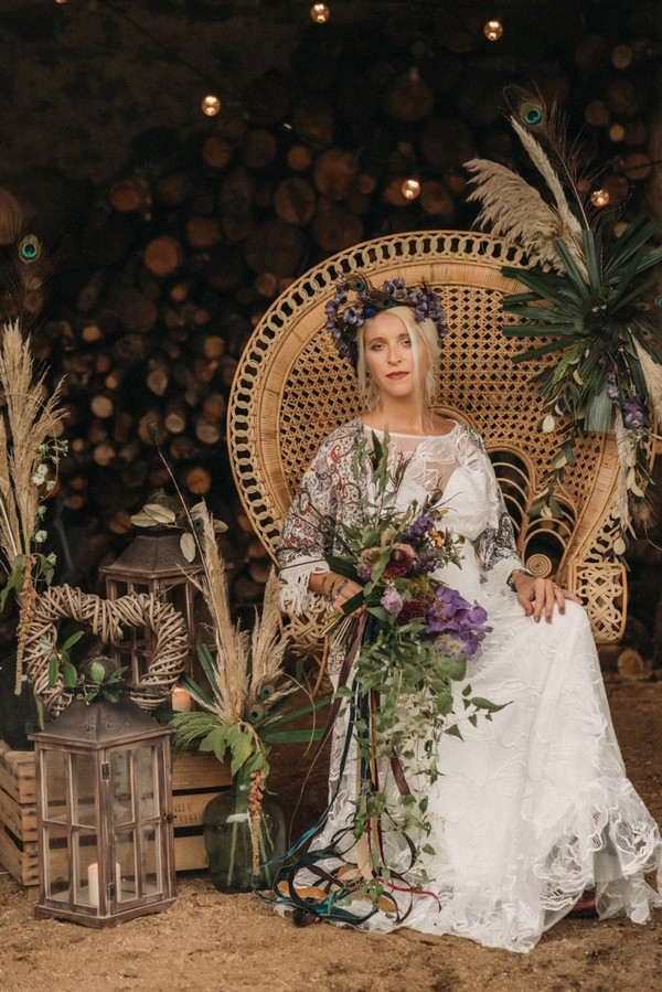 bohemian bride on rattan peacock chairs wearing peacock feather crown