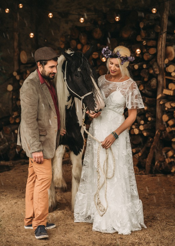 bride and groom stand with black and cream shire horse