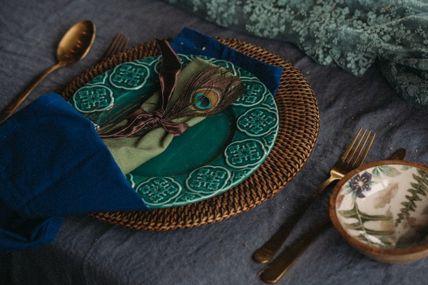 rattan woven round placemat, peacock feather, green napkin, aqua plate and blue tablecloth