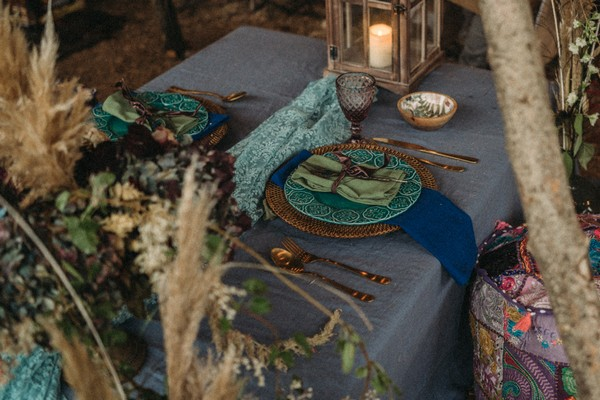 peacock feathers, green napkins, aqua plates and blue tablecloth adorn wedding table